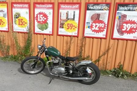 En liten Triumph bobber väntar tålmodigt på sin ägare utanför affären
